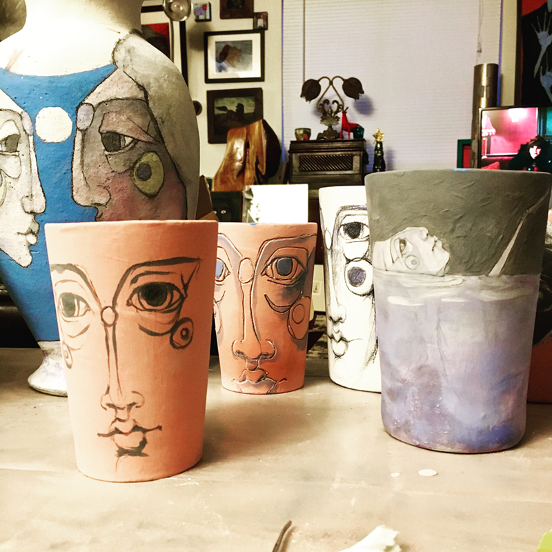"My working ""pile"". The two terra cotta colored cups when fired will be a deep red. When a pencil wasn't enough, I used something like a dental tool to carve the lines into the clay; this is called sgraffito."