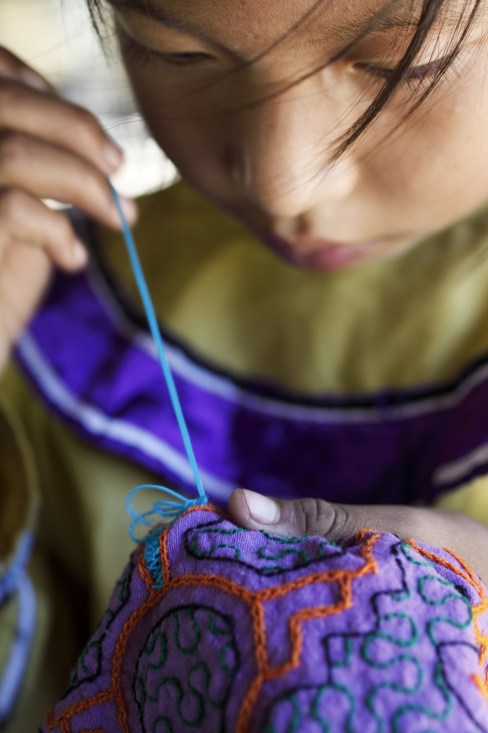 Shipibo girl bent over her embroidery work, practicing the patterns that have made her people internationally renowned as skilled visionary artists (Photo Alianza Arkana)