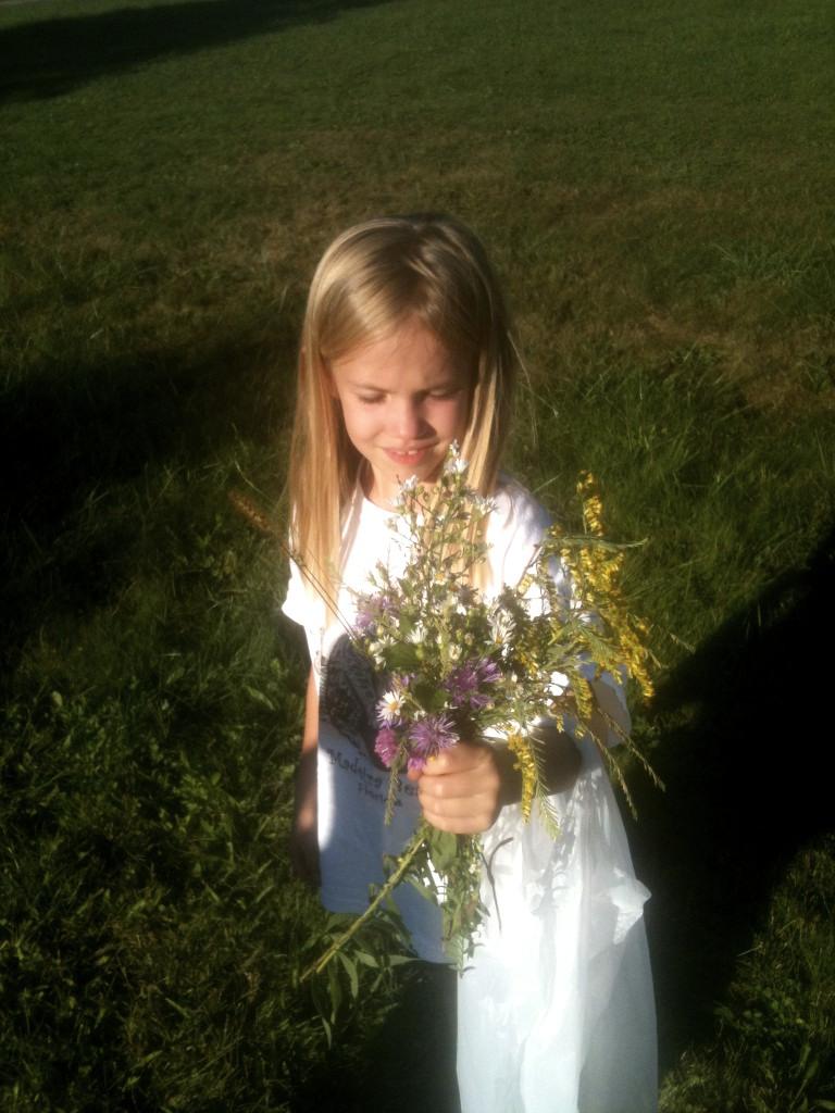 Little girl admiring flowers during outdoor activities