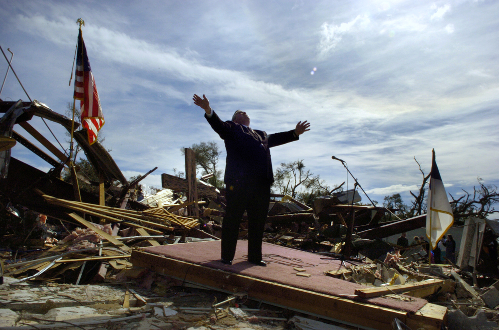 Church Destruction: Rev. Larry Lynn of the Lady Lake Church of God stands on a makeshift pulpit during a praise and worship portion of a morning service Sunday, February 4, 2007 outside the destroyed remains of his church in Lady Lake, Fla. The first of three tornados that killed 20 people in central Florida passed directly over the church. Hundreds of church volunteers from around the state cleared the area of tree debris so a service could be held. Copyright: Sarasota Herald-Tribune
