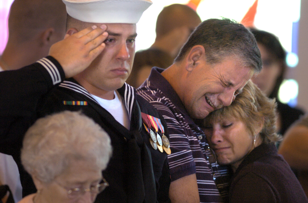 Justin Hall salutes, and parents Kevin and Becky Hall embrace during a memorial service for their brother and son Marine Corps Veteran Eric Hall at Faith Lutheran Church in Punta Gorda, Fla. The missing Marine's body was found in a remote area of Deep Creek after post traumatic stress disorder from the Iraq War caused him to flee a relative's home.