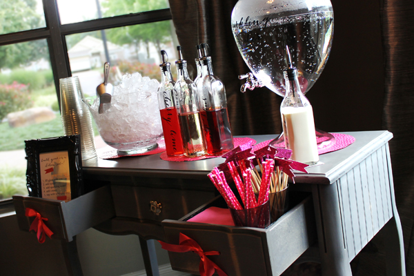 This is an Italian soda bar I did for a shower in August. The venue had a palette of greys and metallics (lots of mercury glass), so I brought in this grey table for the bar, and added pink for a pop of color. I used serveware like the drink dispenser and ice bowl to match the venue's chic, eclectic style.It all worked together to create a cohesive theme.
