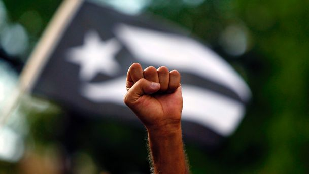 Figure 1:  Man protesting in front of an all-black Puerto Rican flag, a symbol of dissent (Haaretz, 2017).