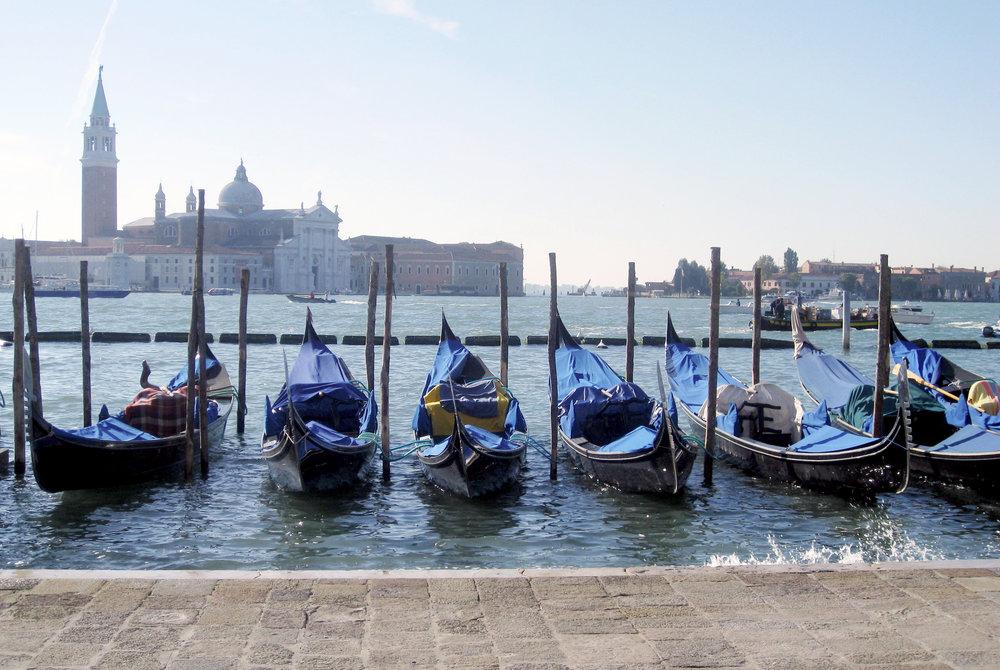 Gondolas in Venice with Murano in the back