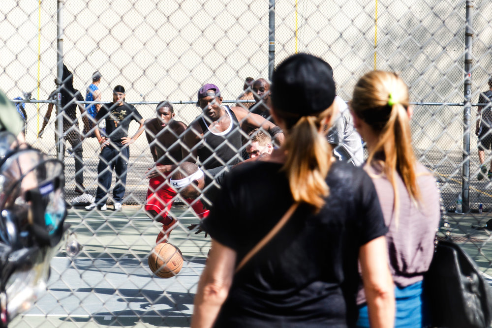 Guys playing a pick-up basketball game with spectators watching.