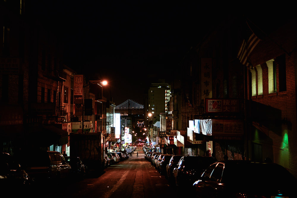 Chinatown at night with the Bay Bridge in back