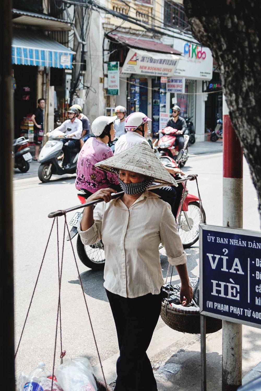 A woman balances baskets while walking in Hanoi