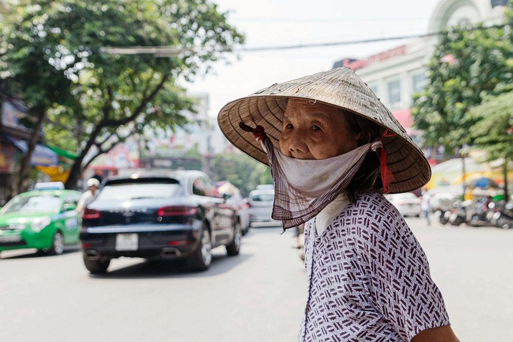 A woman waits to cross the busy street in Hanoi
