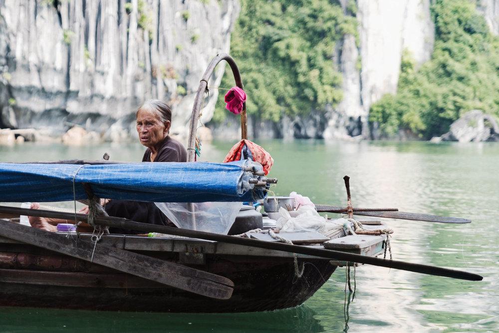 Vietnamese woman sitting in a boat in Ha Long Bay