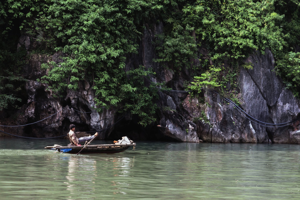 Vietnamese man rowing a boat with his feet in Ha Long Bay