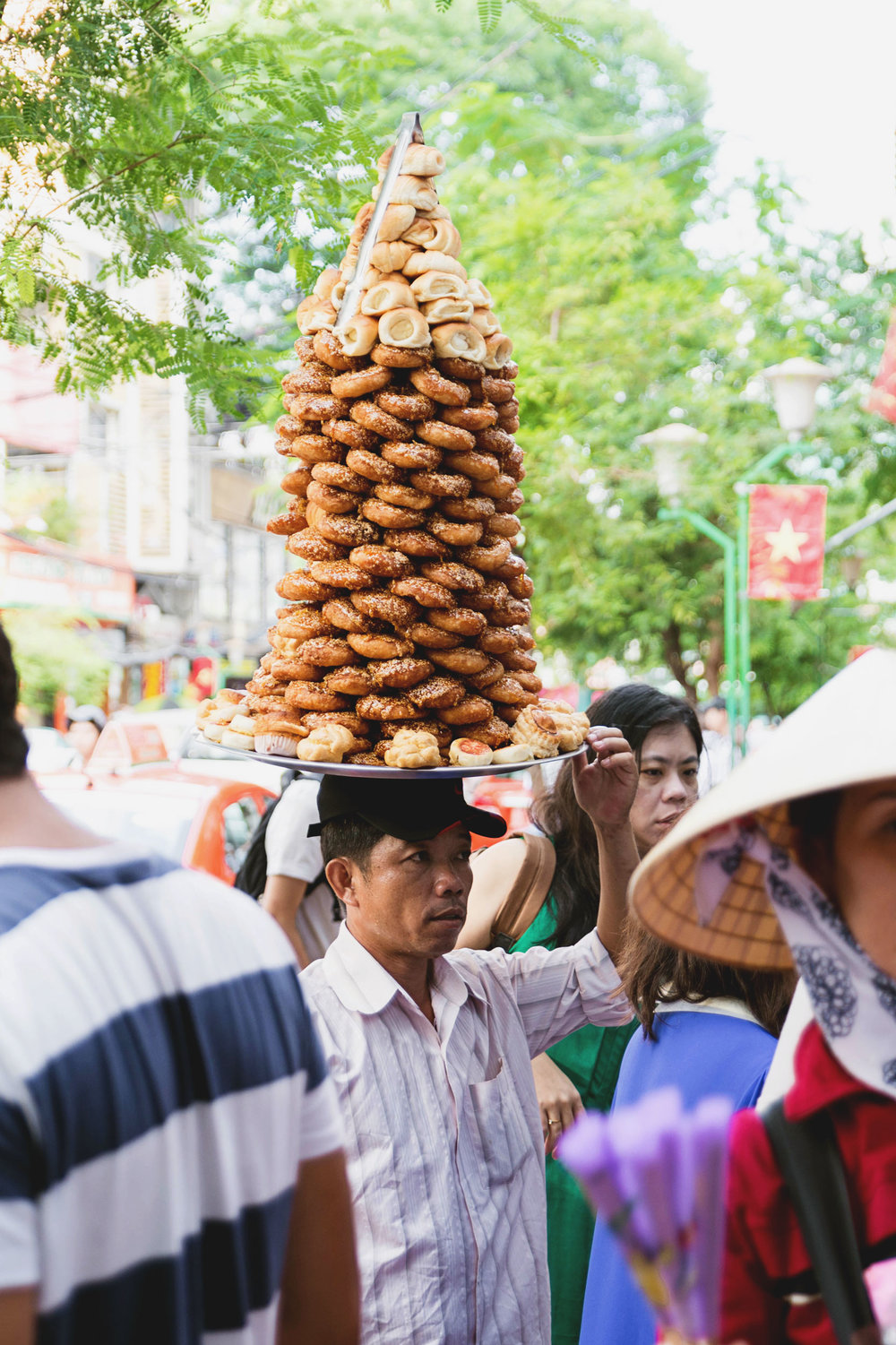 A man holds a tower of pastries on his head in Ho Chi Minh, Vietnam