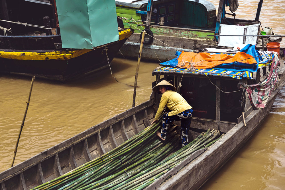 A woman works on a boat in the Mekong river in Vietnam