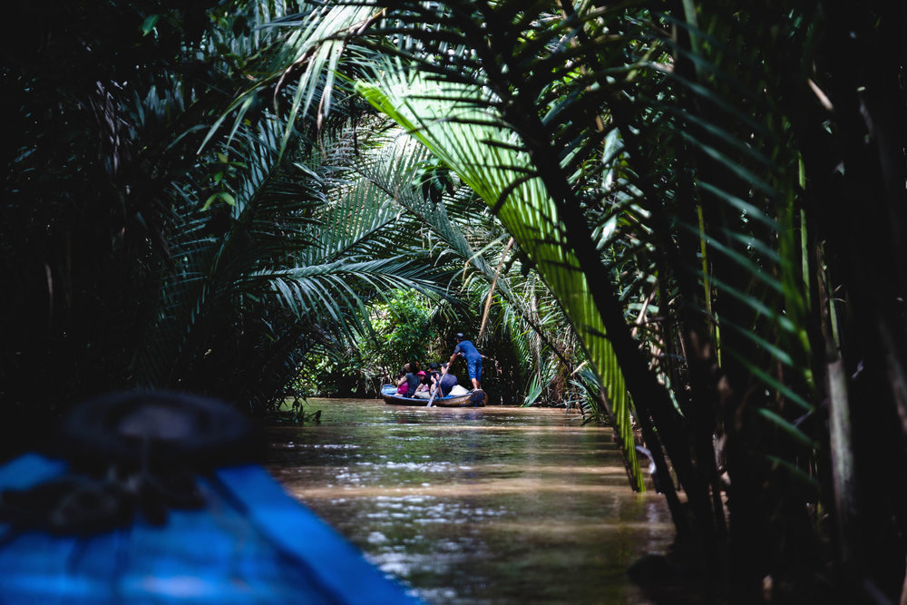 Riding small boats in the dense greens of the Mekong river