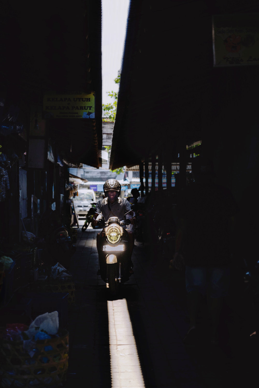 A moped drives through Pasar Taman Sari market
