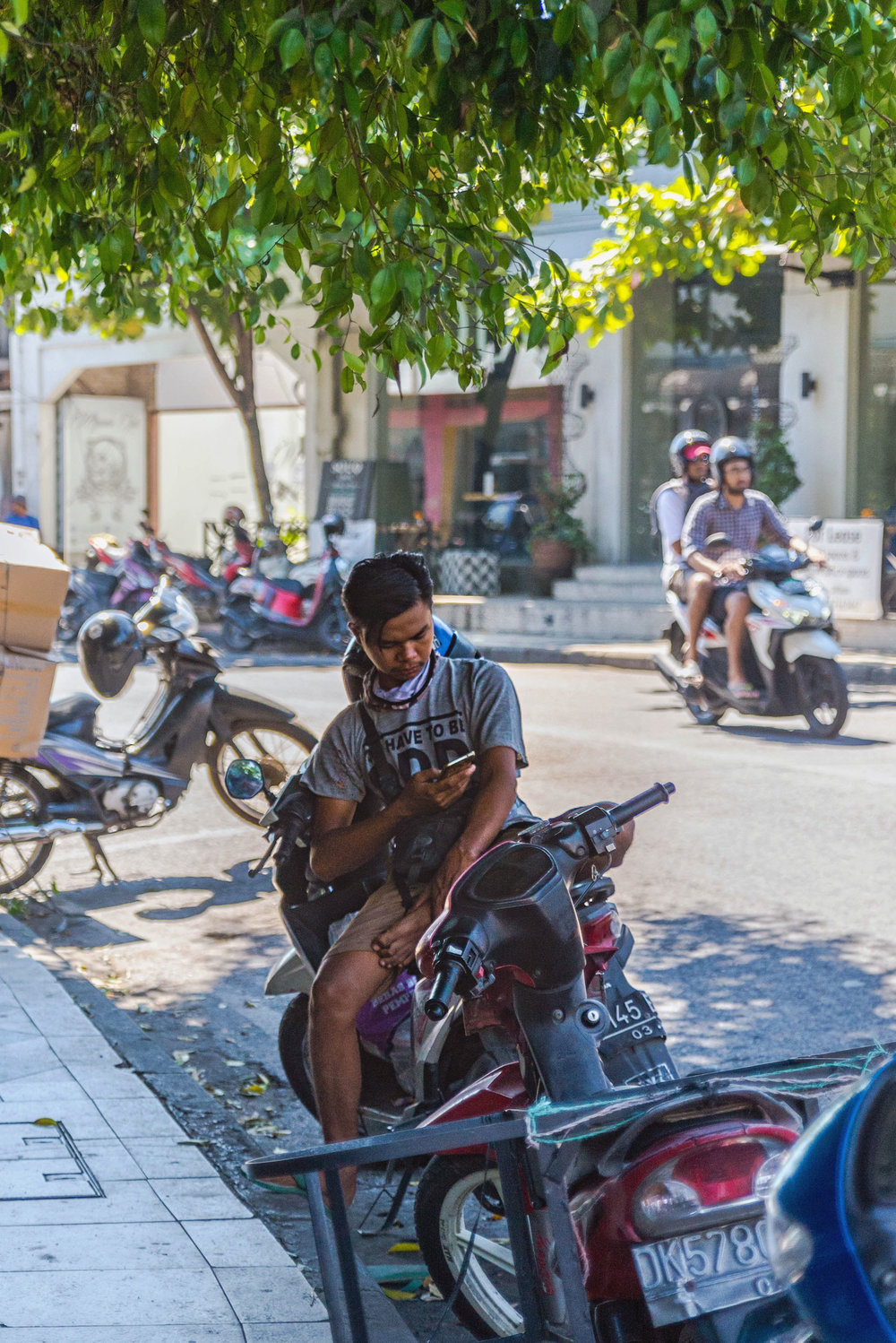 A man sits on his moped in Bali.