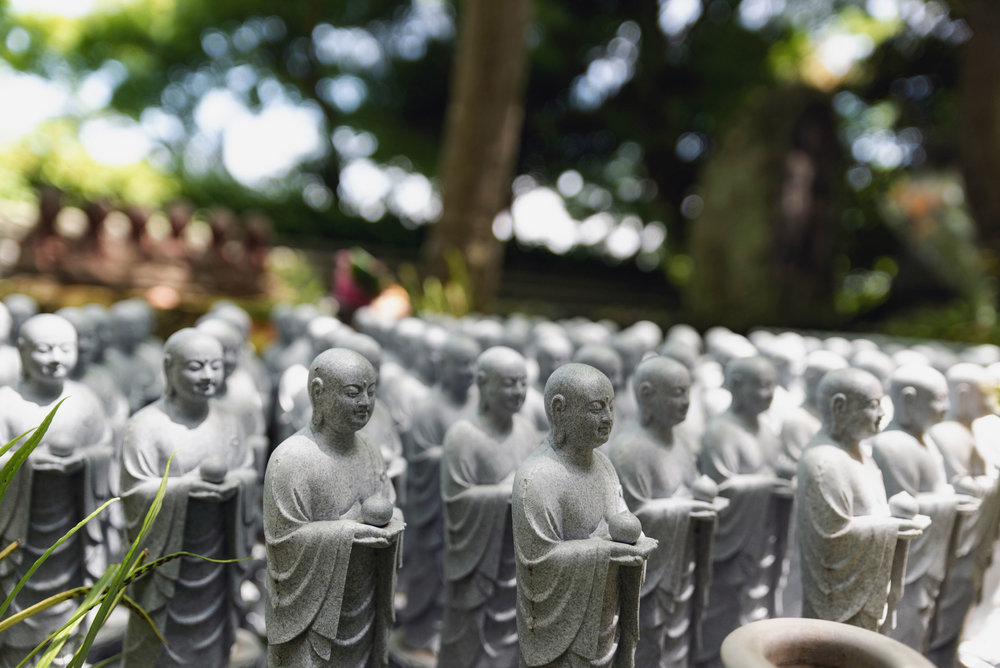 Mini statues beside a walkway at Hase-dera Temple
