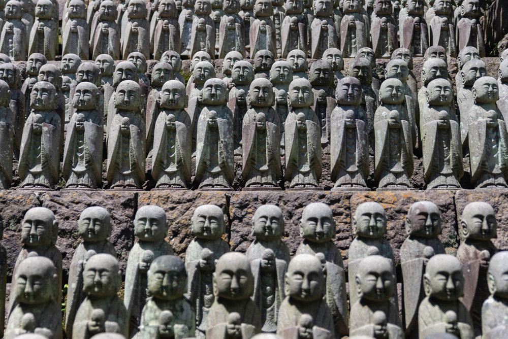 Mini statues lined on a wall at Hase-dera temple