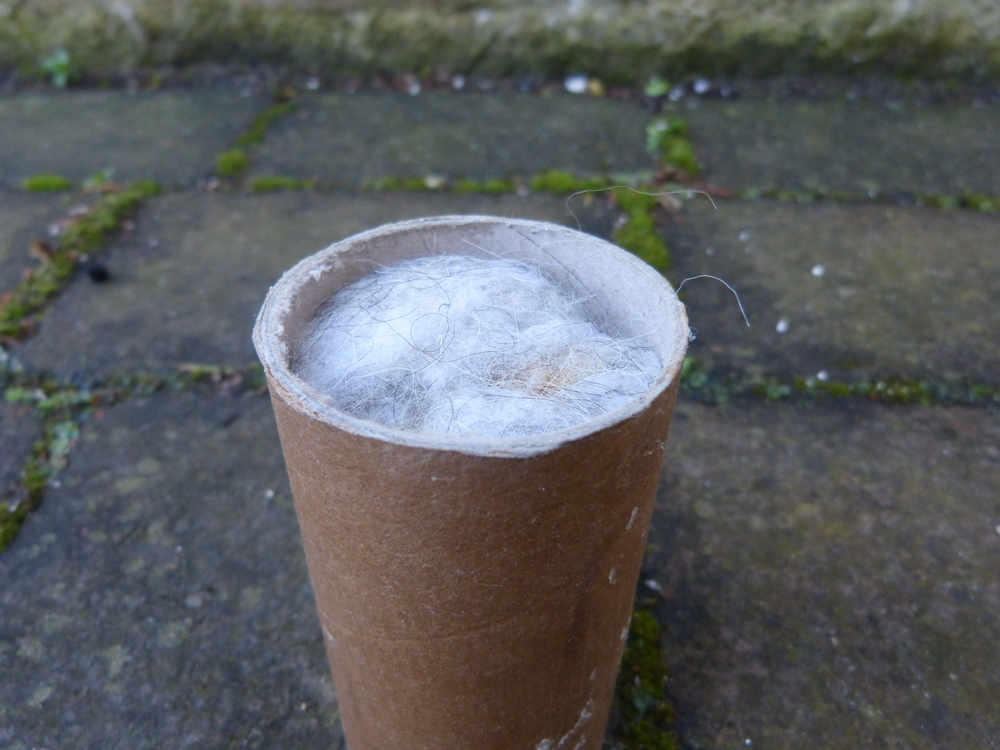 Melted beeswax and linseed oil coated postal tube with sheep wool insulation stuffed inside.