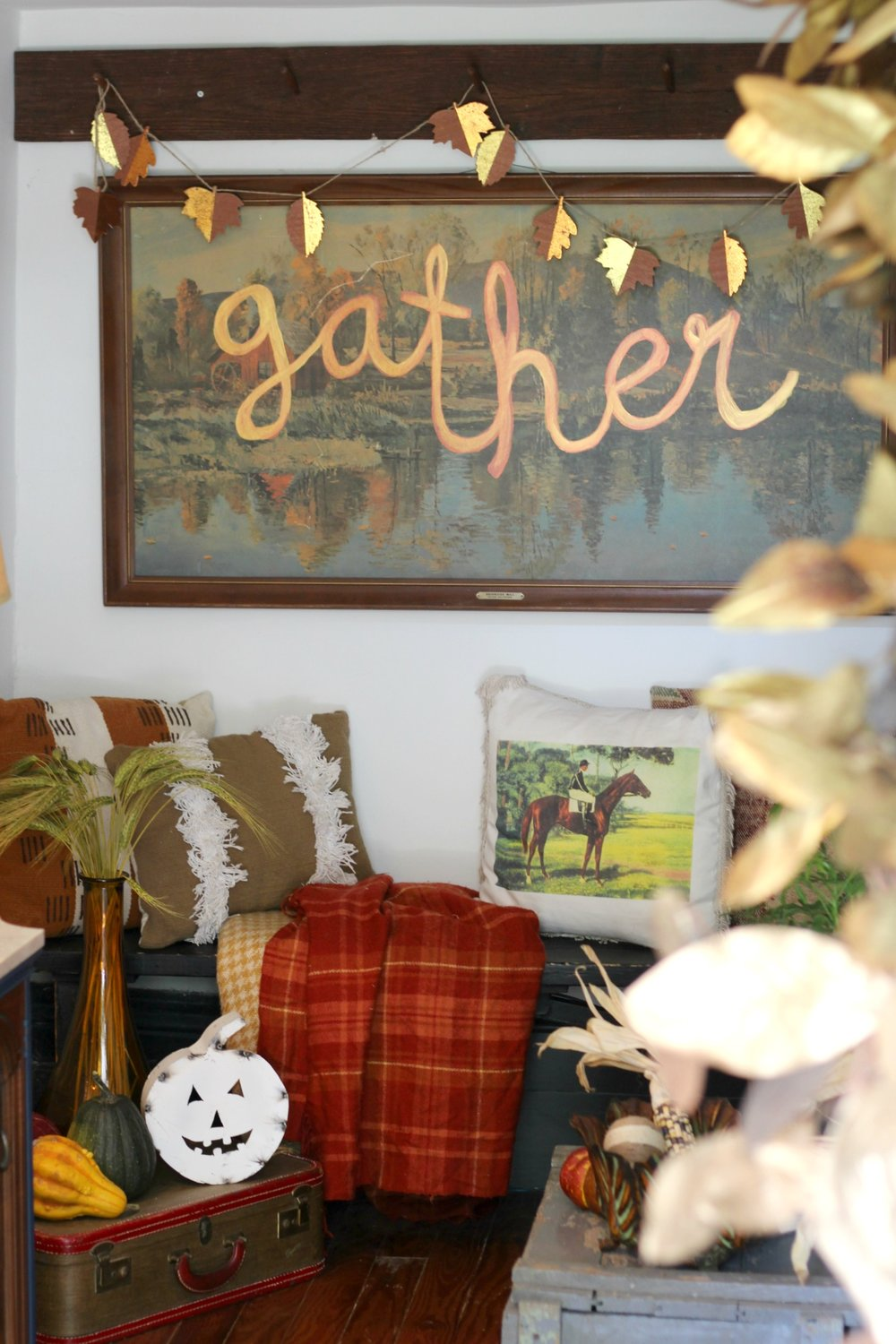 Leaf garland: Target (old)   |   Plaid blankets + horse pillow: thrifted   |    Fringe pillow: Target (old)   |   Suitcase: Thrifted   |   Amber vase: Marshall's    |   White metal jack-o-lantern: Sarah Smith Salvage