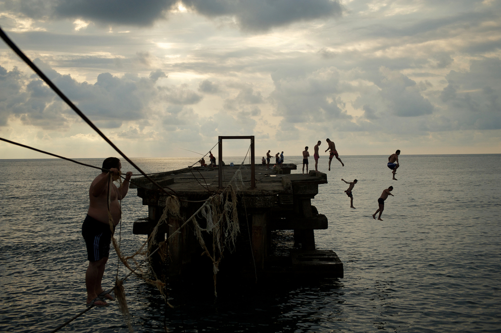 Boys jump from the damage dock to Black sea, Kobuleti, Georgia.
