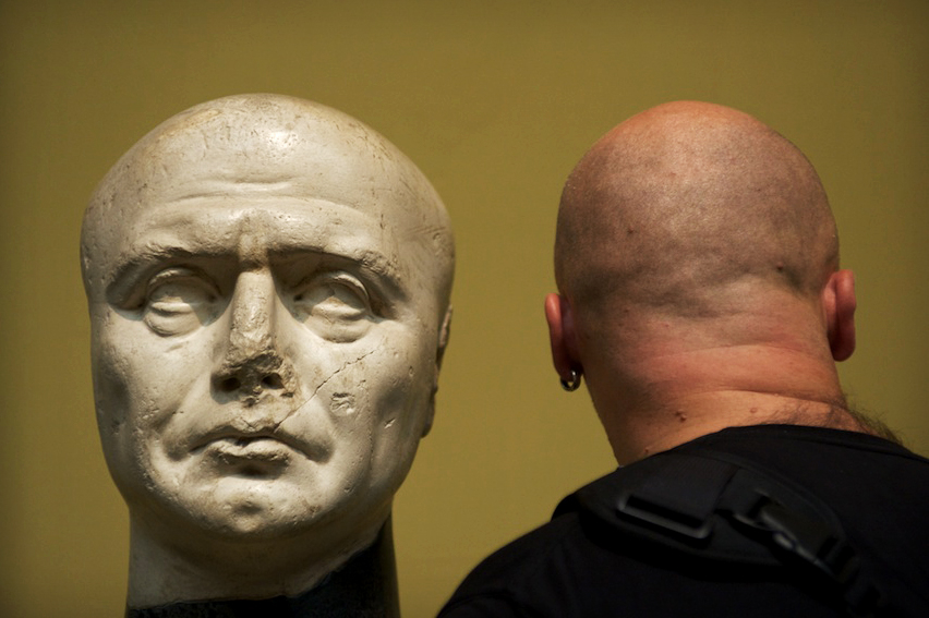 A man stands back near the statue in the Pushkin museum in Moscow, Russia.