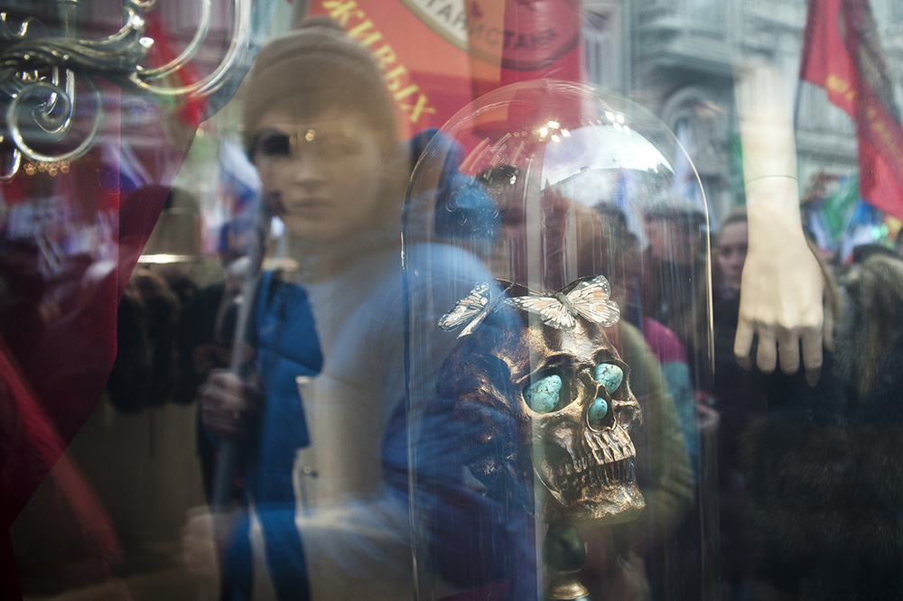 People with flags reflect in a window of a shop. The march of February 21, 2015 dedicated to an anniversary of protests in the Ukraine that started on Kiev's central Independence Square, also known as Maidan.