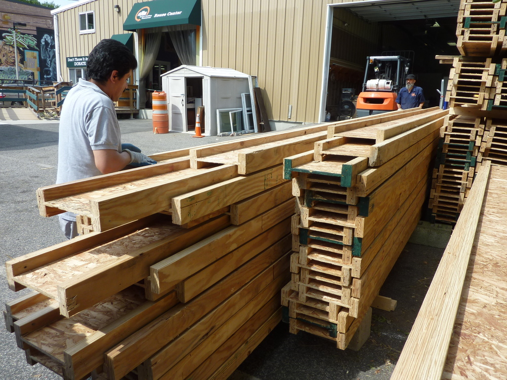 Donated I-beam trusses were unloaded by staffers Miguel Perez, left, and Paul Kiefer.