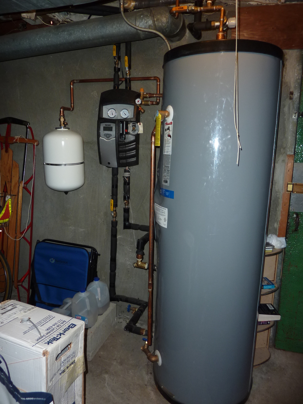 In the basement is a small, white tank for glycol, a pump (center), and an 80-gallon hot water storage tank.
