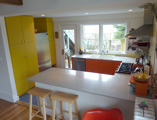 Cabinets in bright custom colors complement neutrals on walls and countertop.