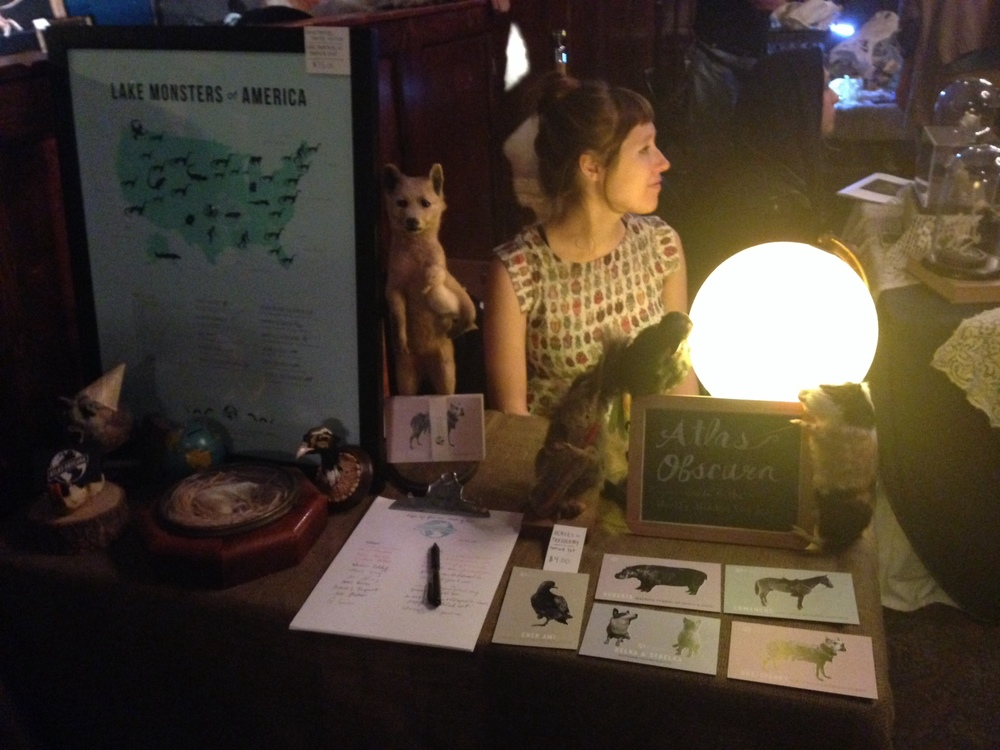 And here is a picture of me manning the Atlas Obscura table, pretending I don't know that Dylan is taking a picture of me.