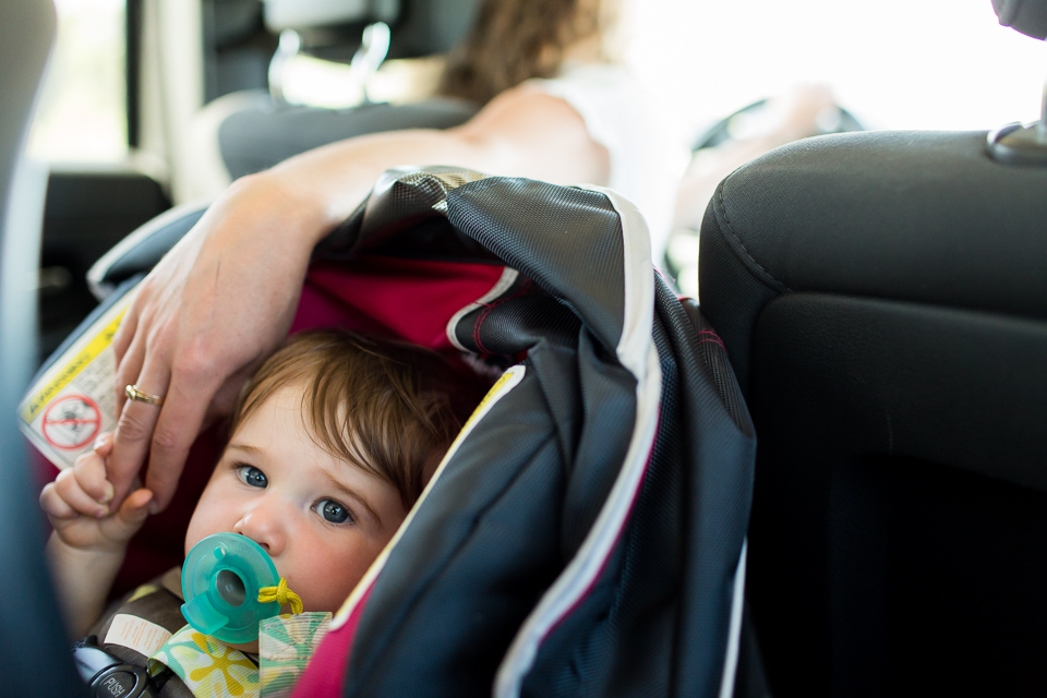 Baby in carseat holding moms hand