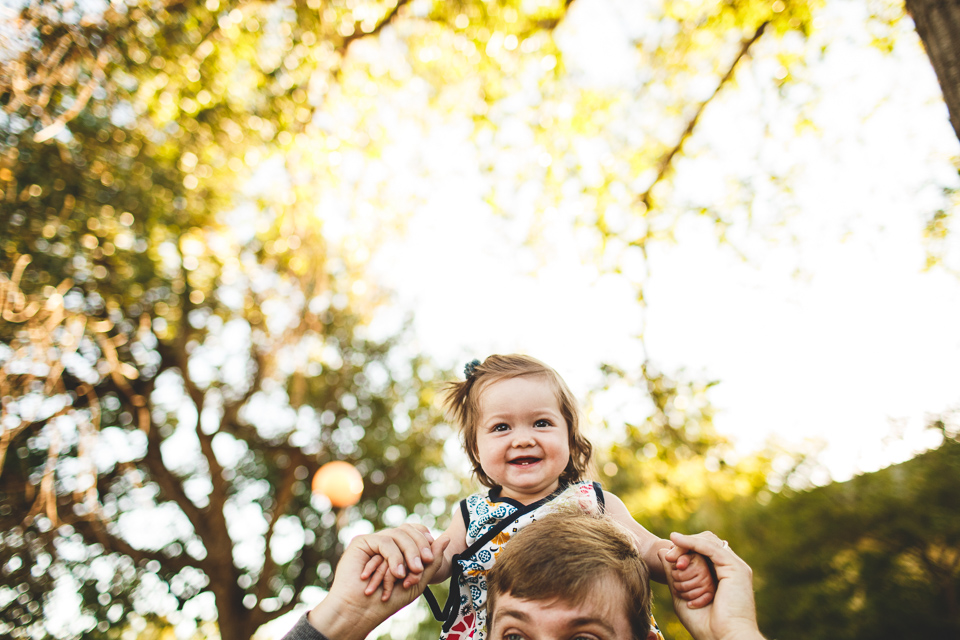 girl on daddy's shoulders at the park