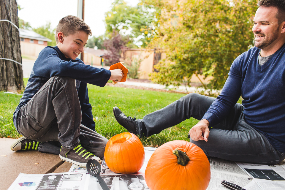 boy carving pumpkin with dad