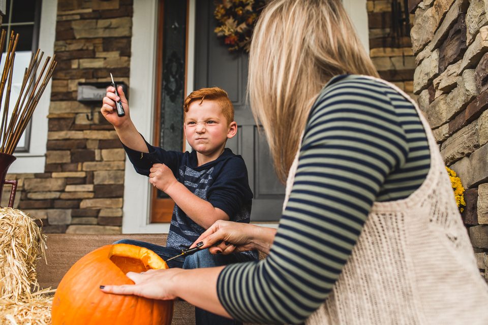 young boy carving pumpkin with mom