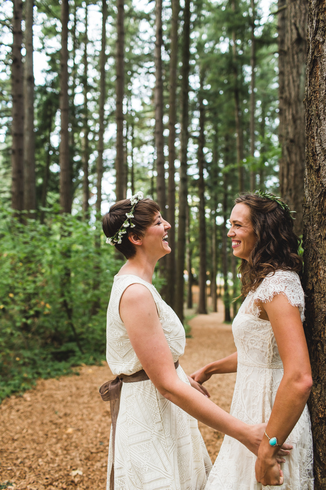 bride and bride laughing in woods at portland oregon same sex wedding