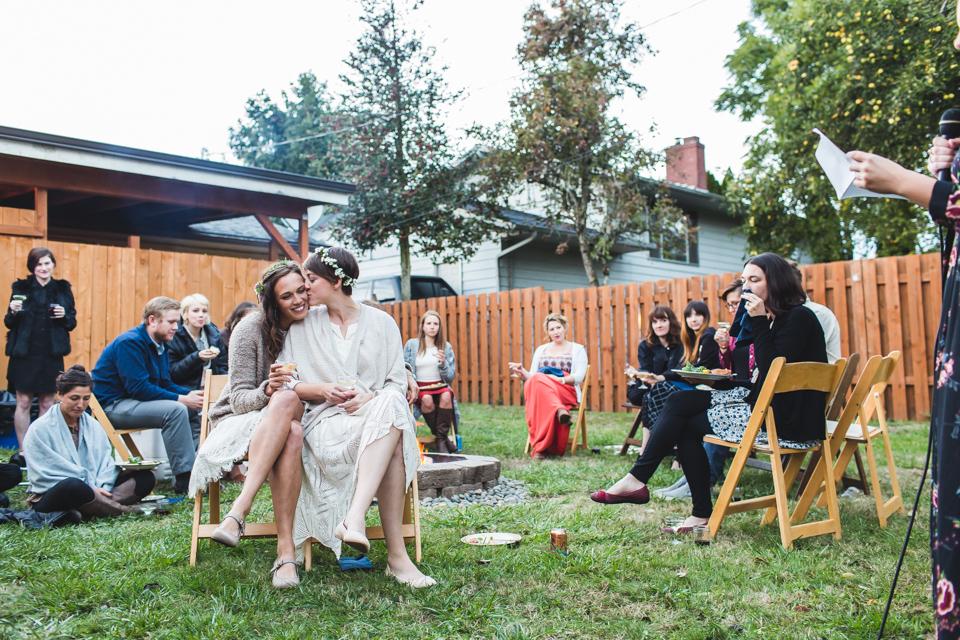 brides listening to toast at backyard same sex portland oregon wedding