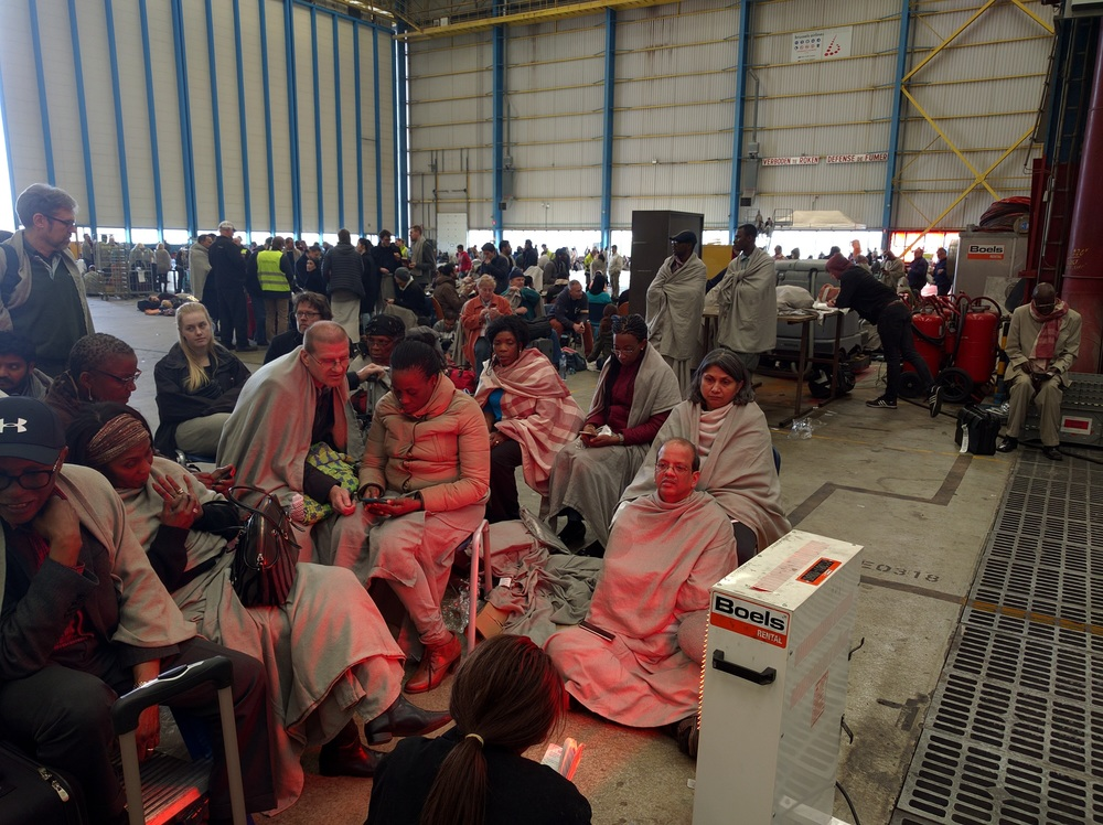 A group of passengers bundled in several blankets huddled around one of the heaters for warmth. This was taken around six hours into our stay inside the hanger.
