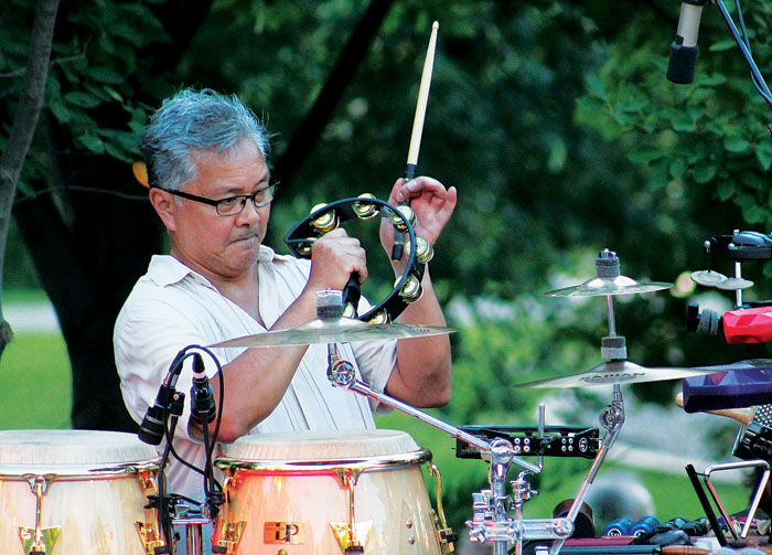 "Percussionist Ralph Dacut plays the tambourine during the annual ""Salute to the Music of Bob Dylan"" Aug. 1 at Veterans' Memorial Amphitheater in St. Louis Park. (Sun Sailor staff photo by Seth Rowe)"
