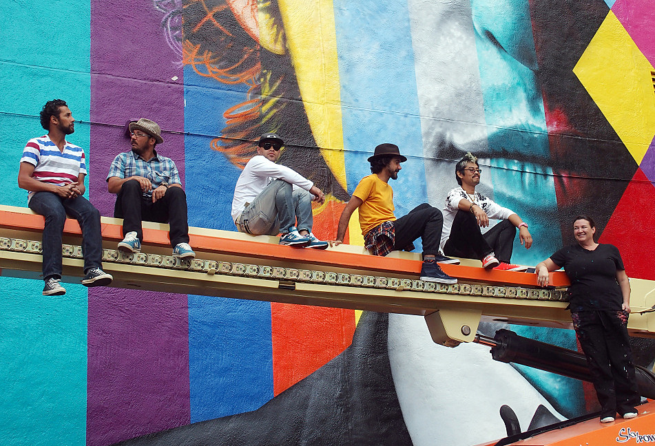 With the mural finished, the crew posed atop the arm of one of the three hydraulic lifts used during the painting. From left to right they are: Agnaldo Brito Pereira, Marcos Rafael da Silva, Silvio Cesar Goncalves de Almeida, Eduardo Kobra, Yuya Nigishi, and Erin Sayer. Nigishi and Sayer are both based in Minneapolis.