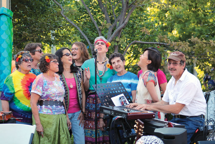 Several members of a choir wore flowers in their hair during a concert celebrating the 50th anniversary of the Summer of Love July 29 in Wolfe Park. (Sun Sailor staff photo by Seth Rowe)