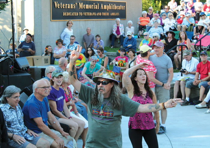 An attendee of the Summer of Love concert flashes peace signs after he joined other veterans recognized July 29 at Veterans' Memorial Amphitheater in St. Louis Park. (Sun Sailor staff photo by Seth Rowe)