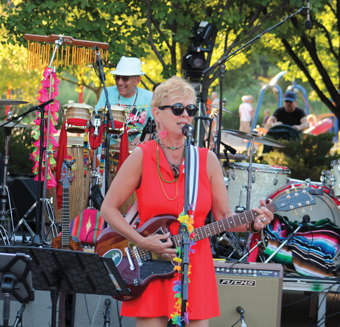 Barbara Meyer plays the guitar and sings at the Summer of Love concert. (Sun Sailor staff photo by Seth Rowe)