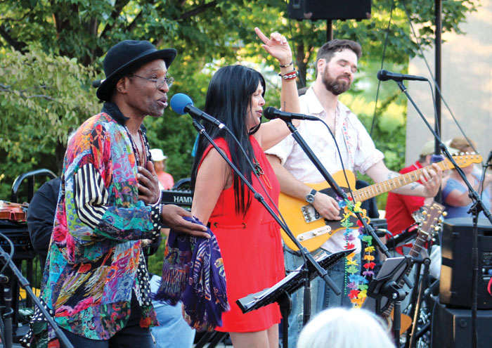 "Stanley Kipper, left, and Barbara Meyer, center, channeled Sonny & Cher while singing ""The Beat Goes On"" during the Summer of Love concert. (Sun Sailor staff photo by Seth Rowe)"