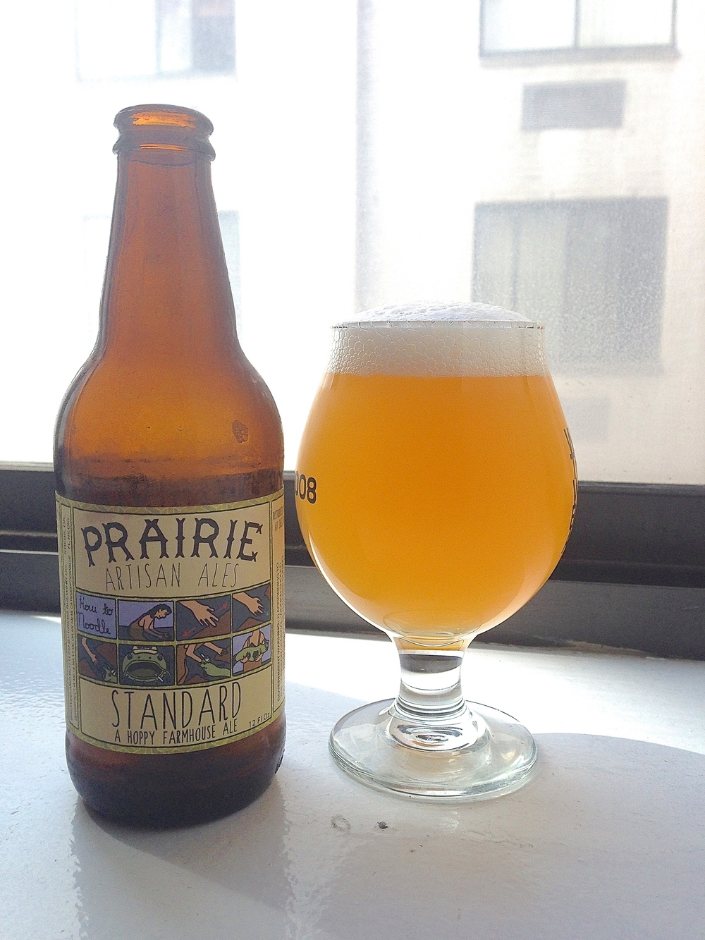 """A Hoppy Farmhouse Ale. Prairie Standard is our everyday beer. Its a light, crisp saison with a hoppy finish. This beer is dry hopped 1lb per bbl with Motueka hops. A lovely New Zealand hop with a spicy lime like flavor and aroma."""