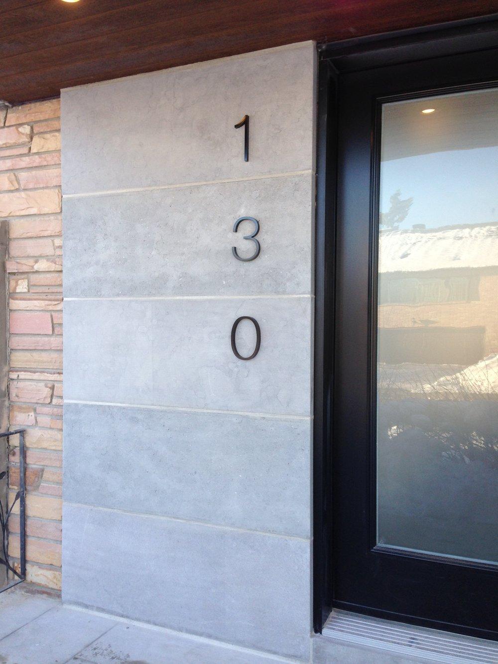 130 - L'espace négatif autour des grands chiffres donne une apparence minimaliste à l'adresse tout en étant facilement visible de la rue.Matériau: aluminiumFini: émail cuit noir semi-lustré