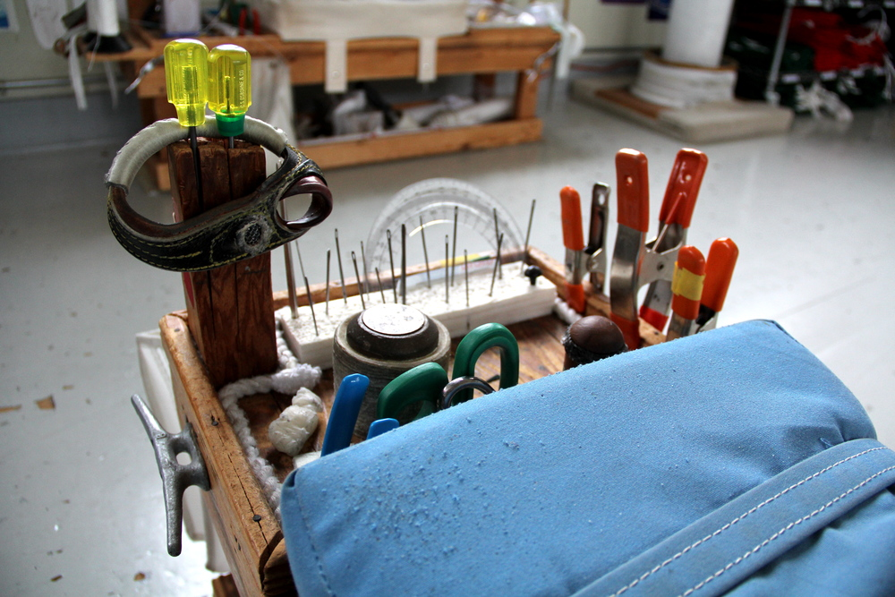 One end of a hand-work bench. There is a leather palm, small stainless steel awls, needles, a mallet, duck-billed pliers, scissors, a wooden fid, clamps, paraffin wax, and protractors for tracing even curves.