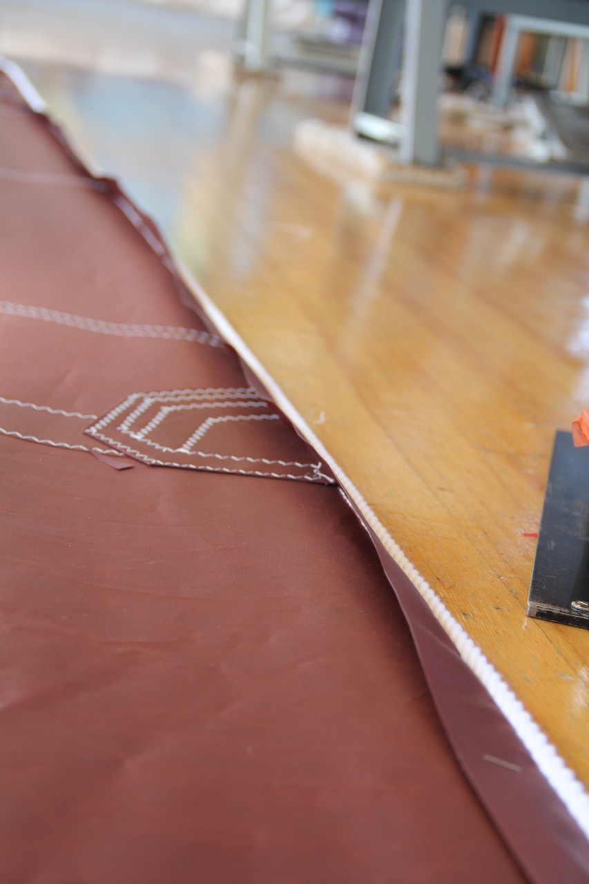 We put the luff edge under tension, as it will be when the sail is set on the sailboat. Then we put the edge tape that has the bolt rope under equal tension and staple it to the edge of the sail. The tape must be pressed precisely against the sail's edge. Then the sail is ready to go back to the sewing machine. Photo by Bonnie Obremski