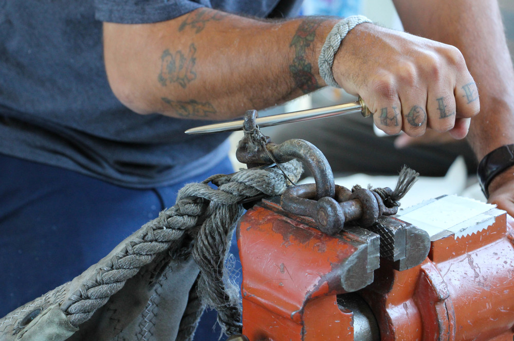 A tall ship sailor assists in a repair job by removing heavy hardware from a sail using a vice and a marlin spike. Photo by Bonnie Obremski.