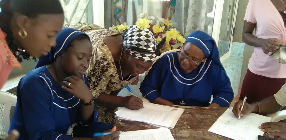 Sister Oresoa sits with members of the Sacred Heart Borrowing Group as they prepare to receive their loans
