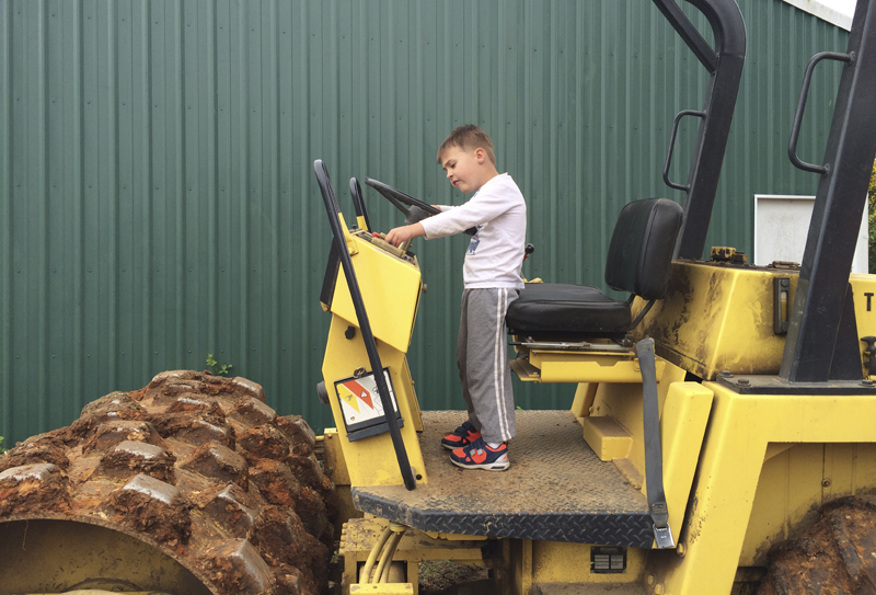 Theo inspects the thing-a-ma-bobber parked next to the existing pole barn.